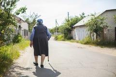 Hogere vrouw die onderaan straat lopen stock afbeeldingen