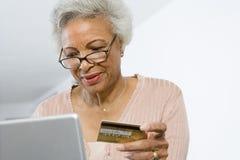 Hogere Vrouw die online winkelen stock foto's