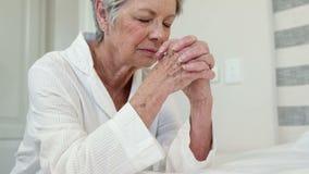 Hogere vrouw die op bed bidden stock videobeelden