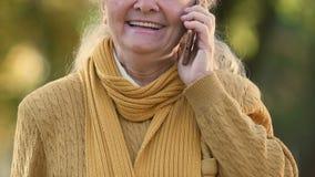 Hogere vrouw die op celtelefoon spreken, gunstige tarieven voor bejaarden, het zwerven stock videobeelden