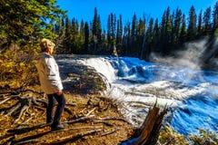 Hogere vrouw die op de Murtle-Rivier letten aangezien het over cusp van Dawson Falls in Putten Gray Provincial Park tuimelt royalty-vrije stock foto's