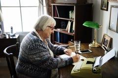 Hogere vrouw die op een document schrijven stock afbeelding
