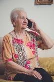 Hogere vrouw die op een mobiele telefoon spreken stock afbeelding