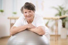 Hogere vrouw die op grijze gymnastiek- bal op fysiotherapiecentrum leunen royalty-vrije stock afbeelding