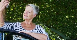 Hogere vrouw die op mobiele telefoon dichtbij auto spreken stock videobeelden