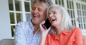 Hogere vrouw die op mobiele telefoon naast de haar mens op bank 4k spreken stock videobeelden