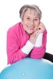 Hogere vrouw die op pilatesbal leunen royalty-vrije stock foto's