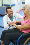 Hogere vrouw die op rolstoel door arts toejuichen Stock Afbeeldingen