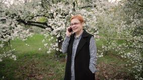 Hogere vrouw die op smartphone in de tuin spreken stock video