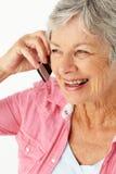 Hogere vrouw die op telefoon spreekt stock afbeelding