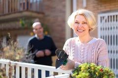 Hogere vrouw die op terras tuinieren stock foto's