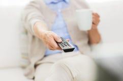 Hogere vrouw die op TV thuis letten en thee drinken Stock Foto