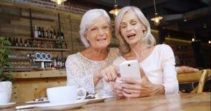 Hogere vrouw die over de telefoon in koffie 4k bespreken stock footage