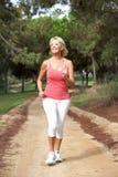 Hogere vrouw die in park loopt Stock Fotografie