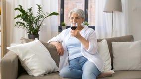 Hogere vrouw die rode wijn van glas thuis drinken stock video
