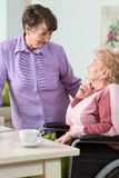 Hogere vrouw die rolstoel gebruiken Stock Afbeelding