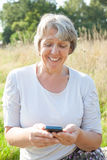 Hogere vrouw die slimme telefoon met behulp van Stock Foto