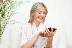 Hogere vrouw die smartphone gebruikt Stock Afbeeldingen