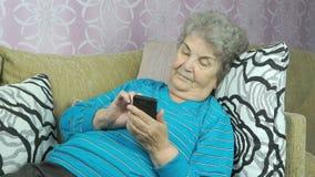 Hogere vrouw die smartphone gebruikt stock videobeelden