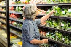 Hogere vrouw die sommige groenten uitkiezen stock afbeeldingen