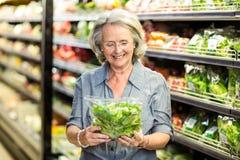 Hogere vrouw die sommige groenten uitkiezen royalty-vrije stock afbeeldingen