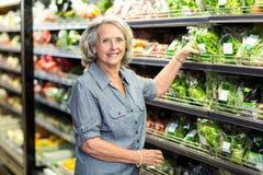 Hogere vrouw die sommige groenten uitkiezen stock foto's