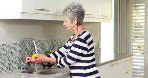 Hogere vrouw die sommige groenten wassen stock videobeelden