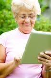 Hogere vrouw die tablet gebruiken stock fotografie