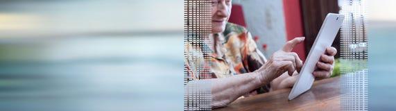 Hogere vrouw die tablet gebruiken Panoramische banner stock afbeeldingen