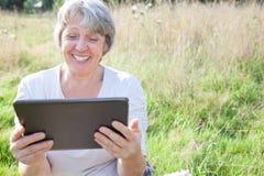 Hogere vrouw die tabletapparaat met behulp van Royalty-vrije Stock Fotografie
