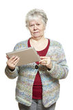 Hogere vrouw die tabletcomputer met behulp van die verward kijken Stock Afbeeldingen