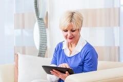 Hogere vrouw die tabletcomputer thuis met behulp van royalty-vrije stock foto