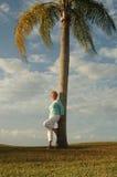 Hogere vrouw die tegen palm leunt Stock Afbeeldingen