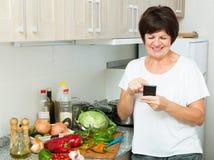 Hogere vrouw die telefoon kijken royalty-vrije stock afbeelding