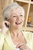 Hogere Vrouw die Telefoon thuis met behulp van Royalty-vrije Stock Foto's