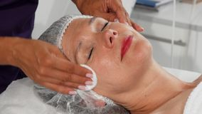 Hogere vrouw die terwijl cosmetologist die haar gezicht met katoenen stootkussens reinigen glimlachen stock fotografie