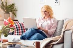 Hogere vrouw die thuis het doorbladeren laptop het geconcentreerde glimlachen zitten stock afbeelding