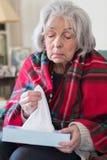 Hogere Vrouw die thuis met Griepvirus lijden stock afbeeldingen