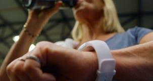 Hogere vrouw die tijd controleren op smartwatch terwijl drinkwater 4k stock video
