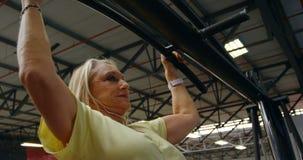 Hogere vrouw die trekkracht-UPS in geschiktheidsstudio 4k doen stock videobeelden