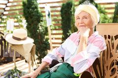 Hogere Vrouw die in Tuin rusten royalty-vrije stock foto