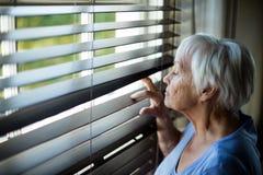 Hogere vrouw die uit blind van venster kijken stock afbeelding