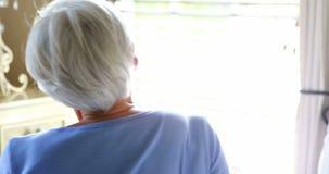 Hogere vrouw die uit van venster kijken stock videobeelden