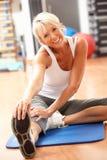 Hogere Vrouw die Uitrekkende Oefeningen in Gymnastiek doet stock afbeelding