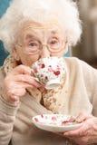 Hogere Vrouw die van Kop thee thuis geniet Royalty-vrije Stock Afbeeldingen