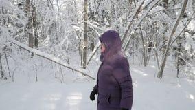 Hogere vrouw die voorbij camera in de winterbos lopen stock footage