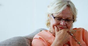 Hogere vrouw die in woonkamer 4k glimlachen stock video