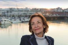 Hogere vrouw door de haven bij zonsondergang Royalty-vrije Stock Foto