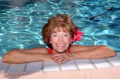 Hogere vrouw door de pool stock foto's