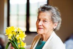 Hogere vrouw door het boeket van de vensterholding van gele narcissen Royalty-vrije Stock Afbeelding